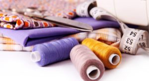 Sewing background with color threads, meter and scissors
